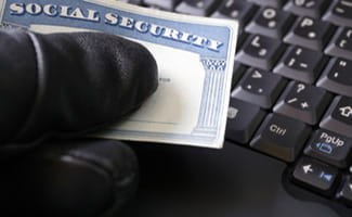man's hand holding social security card