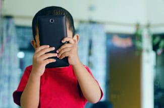 child hiding behind phone