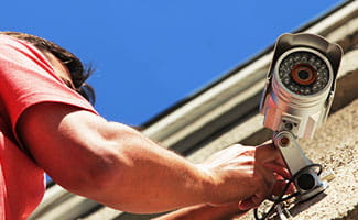 man installing outdoor security camera