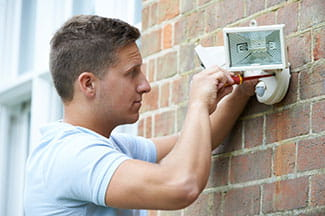 man installing security lights