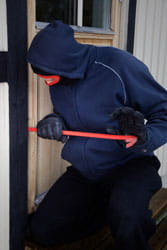 Burglar breaking into a home with crowbar