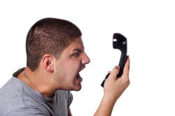 Man receiving an annoying, unsolicited phone call