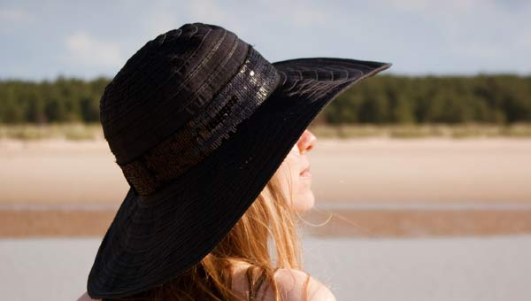 Lady wearing summer hat at beach